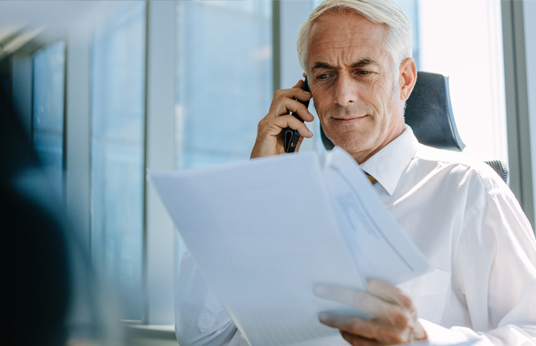 Business man on phone while reading documents