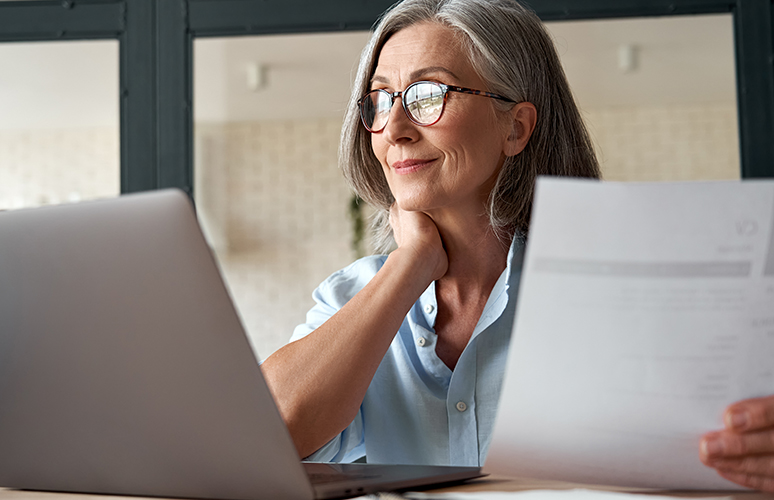 Woman holds paper while looking at laptop
