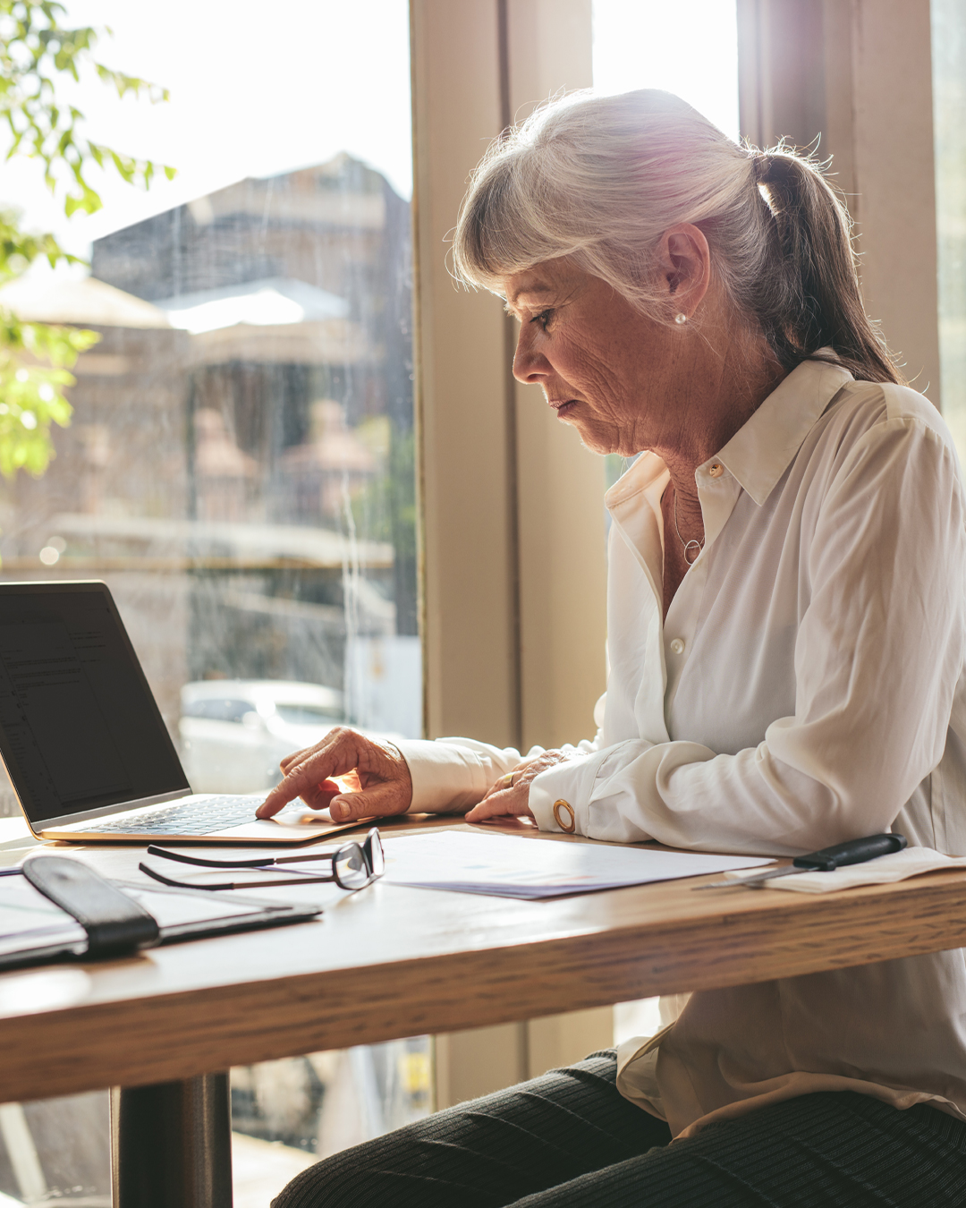 Woman looks at laptop and papers